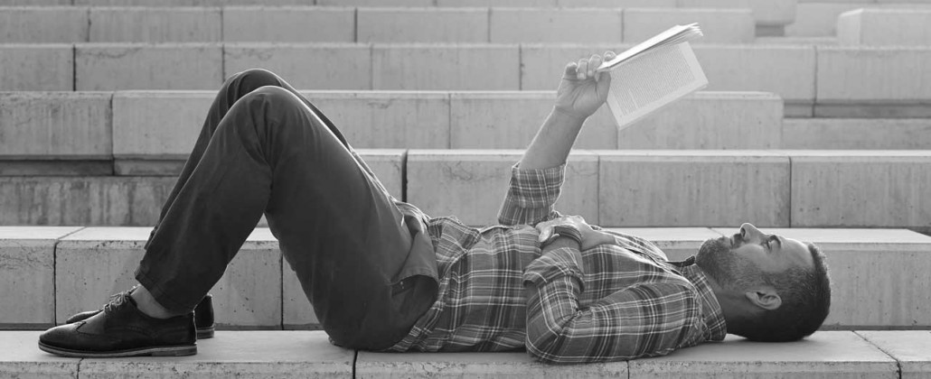 Black and White photo of a Man reading on the steps