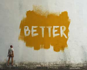 "Man looking at wall with ""Better"" painted on it"