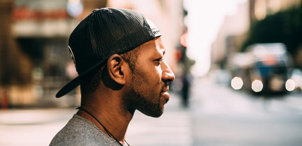 Man with hat backwards, looking sideways on city street