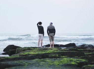 Two men talking on beach