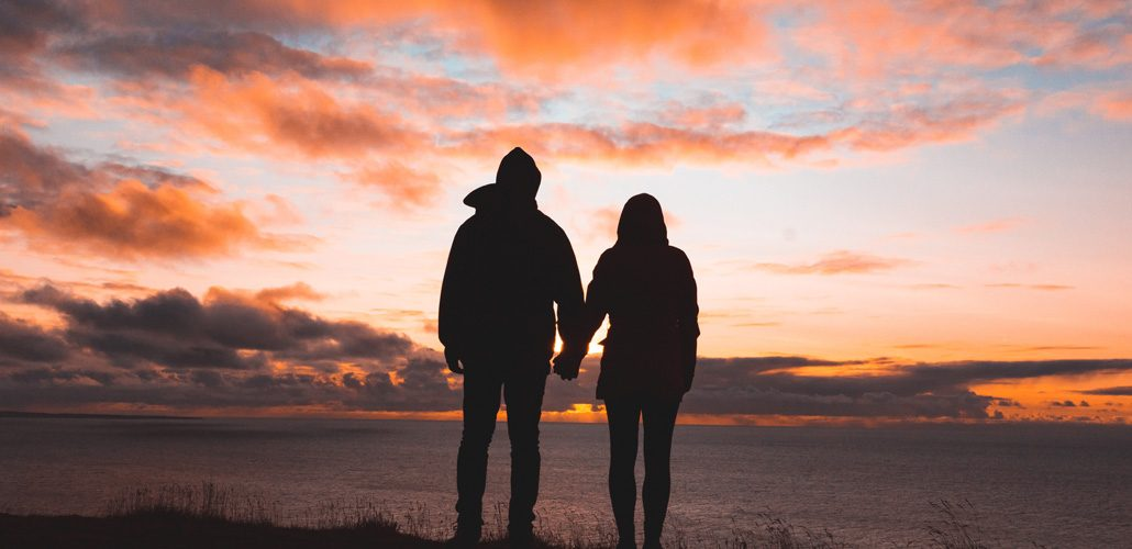 Couple holding hands and watching sunset