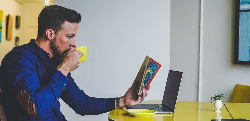 Man reading book with laptop