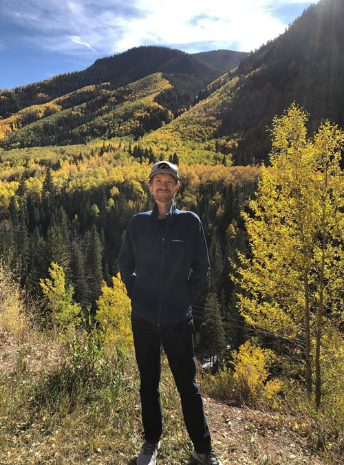 Jason standing with forested hills behind him