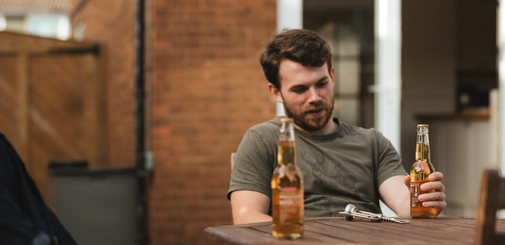 Man seated drinking a beer with a friend